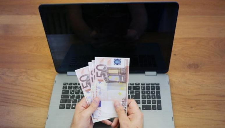 Laptop mit Hand und vielen 50 Euro Scheinen